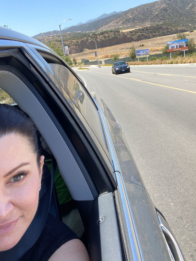 Selfie of Jen Stoddard in her car, pulled over on the side of the road, with another car in the background.