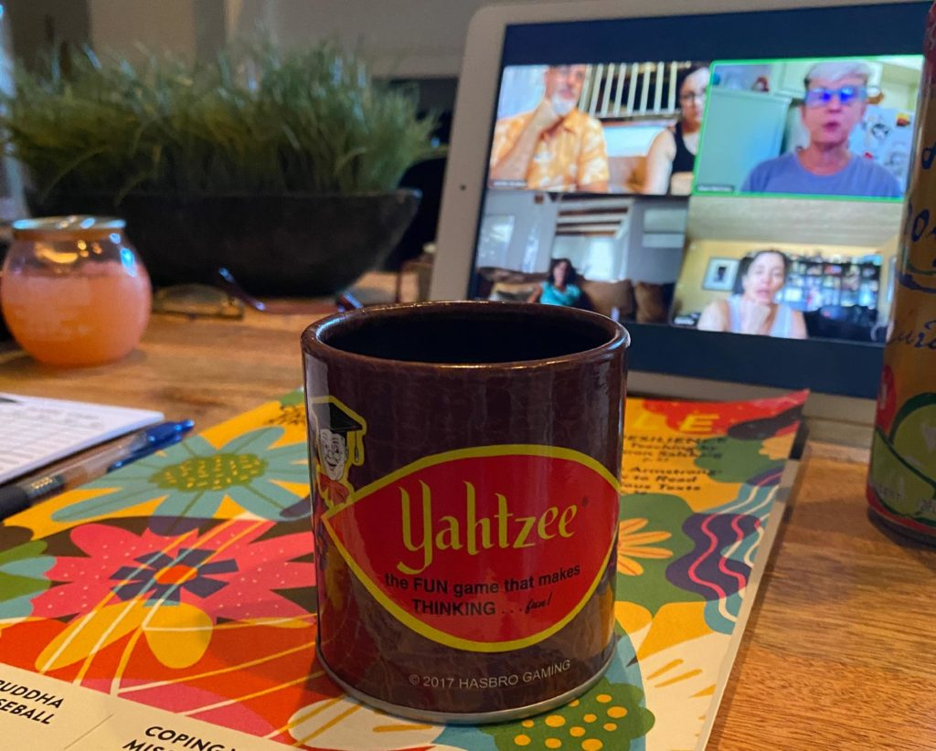 A Yahtzee-branded coffee cup with a tabled in the background, showing an ongoing video call.