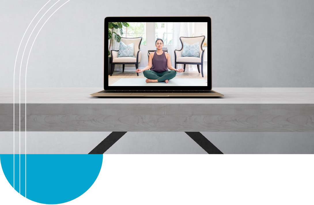 Yoga video playing on laptop on table.